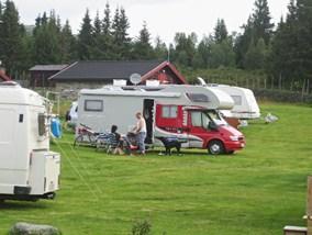 Bilde av campingplassen. Overnattingsgjestene sitter utenfor sin bobil og nyter morgenen i Rondane