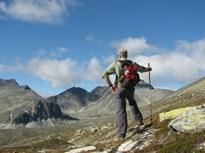 Bilde som viser mann som går på fjelltur i fjellheimen i Rondane nasjonalpark