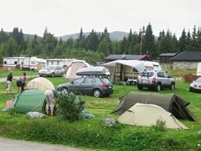 Bilde av campingplassen i Gudbrandsdalen med biler, telt og campingvogner som overnattes i