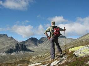 Fin utsikti over Rondane Nasjonalpark. Bilde av mann på fjelltur som speider opp mot fjellene