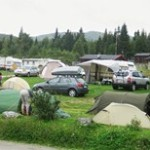 Bilde som viser campingplassen i Ringebu med telt, campingvogn og biler sommerstid